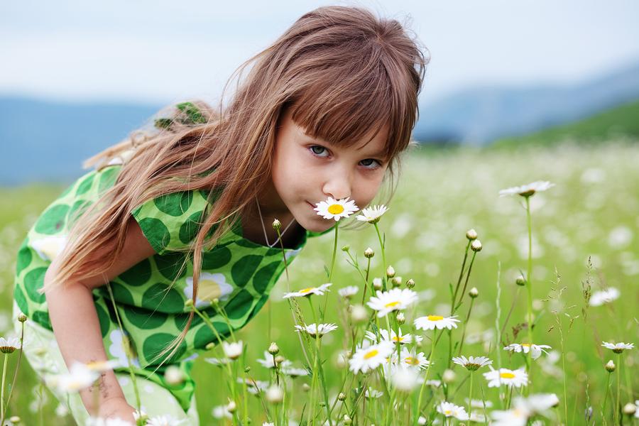 ילדה מריחה פרחים בשדה